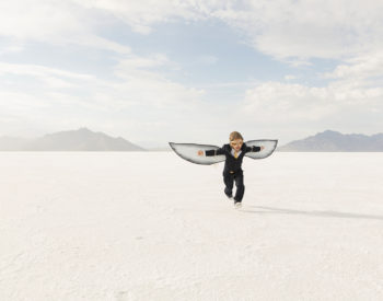 A young business boy dressed in business suit and wearing cardboard wings and aviator goggles is ready to fly his business into the sky. He is running on the Bonneville Salt Flats in Utah, USA.
